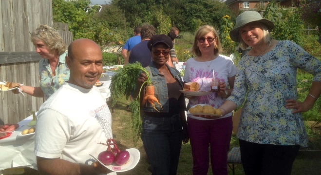 Happy plot holders showing off their winning entries. Onions: 1st prize, Carrot: Runner up in ugliest vegetable category, Coffee cake and Strawberry/Rhubarb jam: 1st prize in both categories, Potatoes: 1st prize
